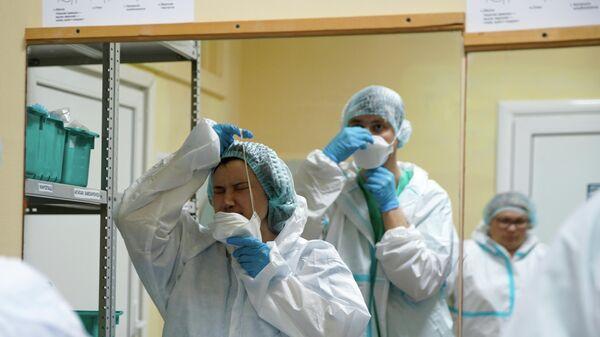 Медицинские работники надевают средства индивидуальной защиты перед входом в красную зону в госпитале для зараженных коронавирусной инфекцией COVID-19 в Твери