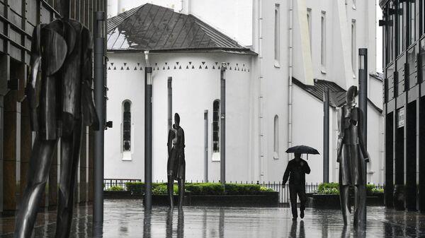 Прохожий во время дождя на пешеходной площади бизнес-центра Белая Площадь в Москве