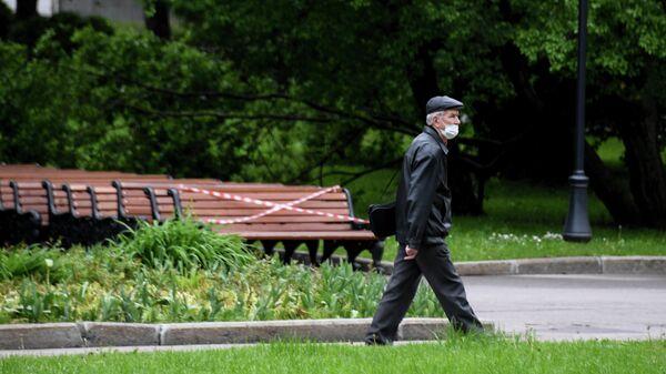Мужчина в защитной маске гуляет в Центральном парке культуры и отдыха имени Горького, который вновь открылся для посещений в рамках второго этапа снятия ограничений в Москве