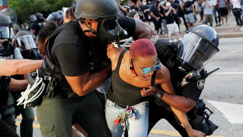 Сотрудники полиции арестовывают протестующую в Атланте, США