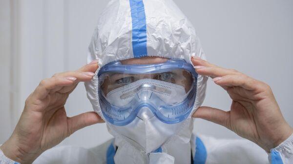 Медик надевает защитный костюм на входе в красную зону