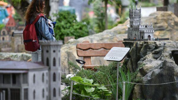Женщина с ребенком у макета Памятника архитектуры Ласточкино гнездо в Бахчисарайском парке Крым в миниатюре на ладони