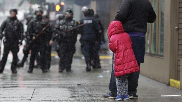 Девочка рядом с отцом во время протестов в Вашингтоне