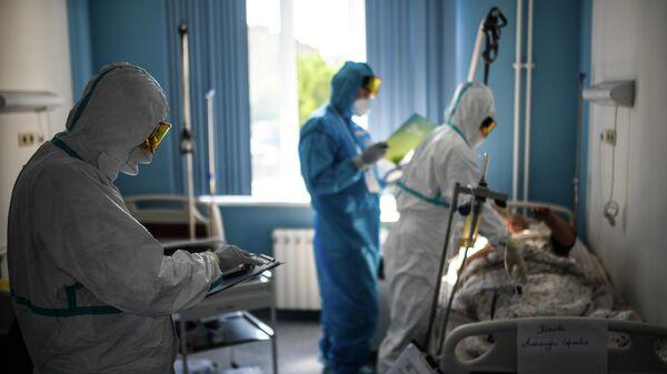 Врачи у постели пациента во время обхода в госпитале COVID-19 в ЦИТО им. Н. Н. Приорова