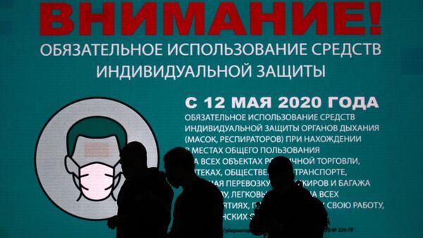 Люди около информационного баннера в аэропорту Шереметьево в Москве