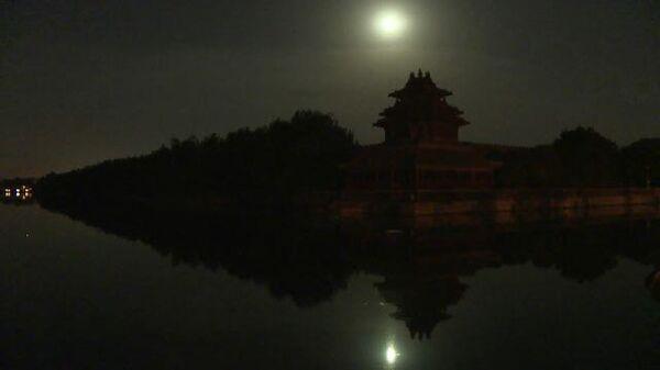 """""""Клубничная"""" Луна: полутеневое затмение в небе над Пекином"""