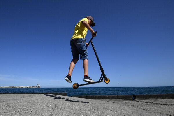 Мальчик катается на самокате на набережной в Ялте
