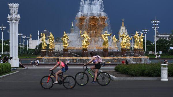 Посетители ВДНХ проезжают на велосипедах мимо фонтана Дружба народов