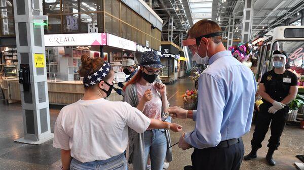Сотрудник измеряет температуру посетителям на входе в фудмолл Депо. Москва