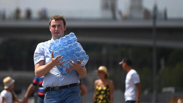 Прохожий с упаковкой питьевой воды в окрестностях парка Зарядье в Москве