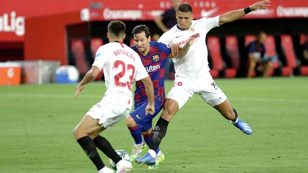 Barcelona's Argentinian forward Lionel Messi (C) challenges Sevilla's Spanish defender Sergio Reguilon (L) and Sevilla's Brazilian defender Diego Carlos (R) during the Spanish league football match between Sevilla FC and FC Barcelona at the Ramon Sanchez Pizjuan stadium in Seville on June 19, 2020. (Photo by CRISTINA QUICLER / AFP)