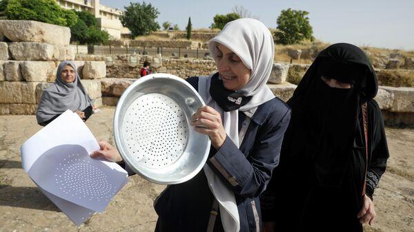 Женщины наблюдают солнечное затмение в Аммане, Иордания