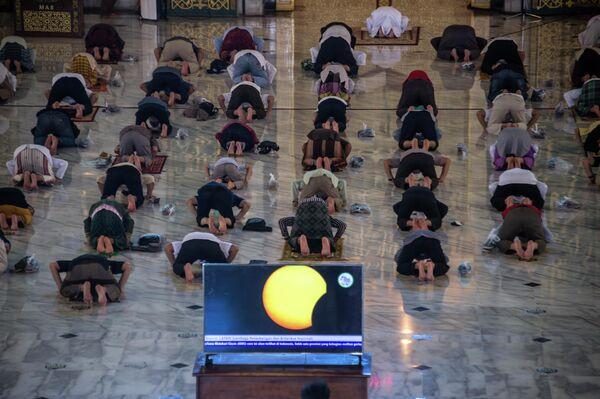 Прихожане молятся во время солнечного затмения в мечети города Сурабая, Индонезия