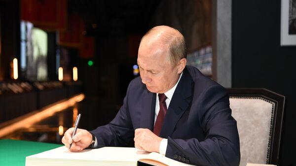 Президент РФ Владимир Путин оставляет запись в книге почетных посетителей во время посещения главного храма Вооружённых Сил