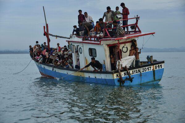 Лодка с людьми из народности рохинджа из Мьянмы прибывает на берег в Северный Ачех