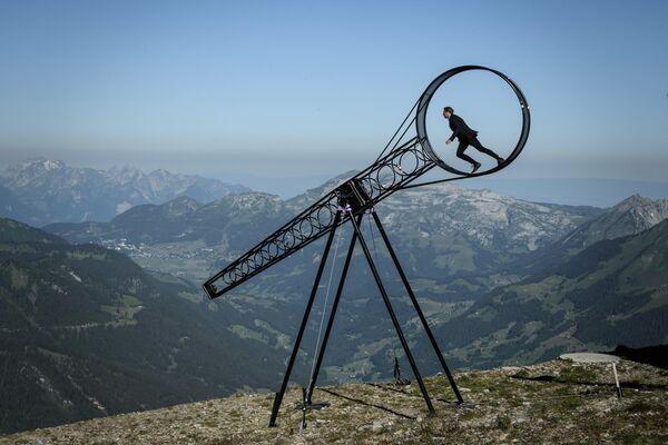 Акробат Рамон Катринер исполняет серию трюков на колесе смерти, установленном над пропастью в швейцарских Альпах