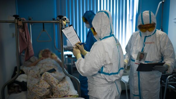 Врачи у постели пациента во время обхода в госпитале для лечения зараженных коронавирусной инфекцией в ЦИТО им. Н. Н. Приорова