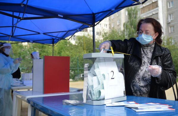 Женщина во время голосования по вопросу принятия поправок в Конституцию РФ на мобильном избирательном пункте во дворе жилого дома в Екатеринбурге
