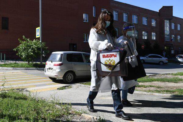Члены участковой избирательной комиссии во время выездного голосования в Новосибирске по вопросу принятия поправок в Конституцию РФ