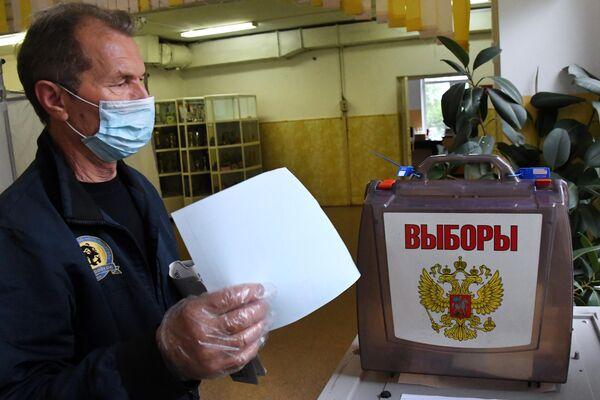 Мужчина голосует по вопросу внесения поправок в Конституцию РФ на избирательном участке во Владивостоке