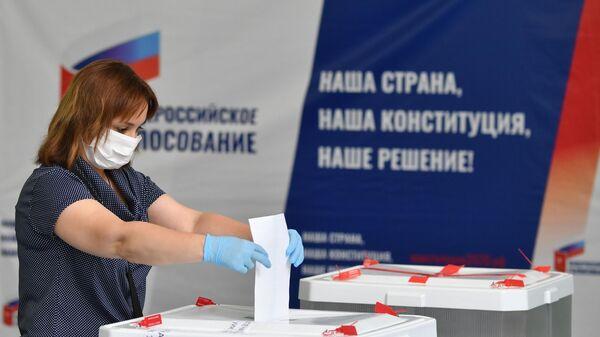 Женщина голосует по вопросу внесения поправок в Конституцию РФ на избирательном участке в Москве