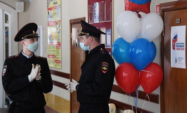 Сотрудники полиции дежурят во время голосования по вопросу одобрения изменений в Конституцию России на избирательном участке в средней школе №6 во Владивостоке