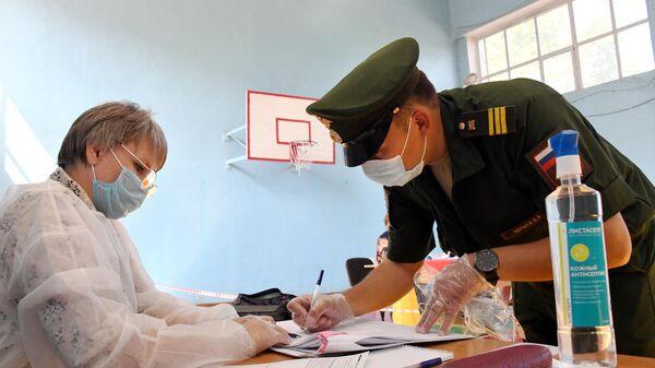 Военнослужащий голосует по вопросу одобрения изменений в Конституцию РФ на избирательном участке в поселке Песчанка