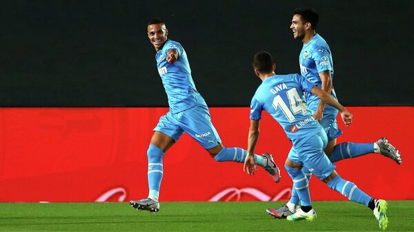 Нападающий Валенсии Родриго Морено празднует гол в ворота мадридского Реала с одноклубниками