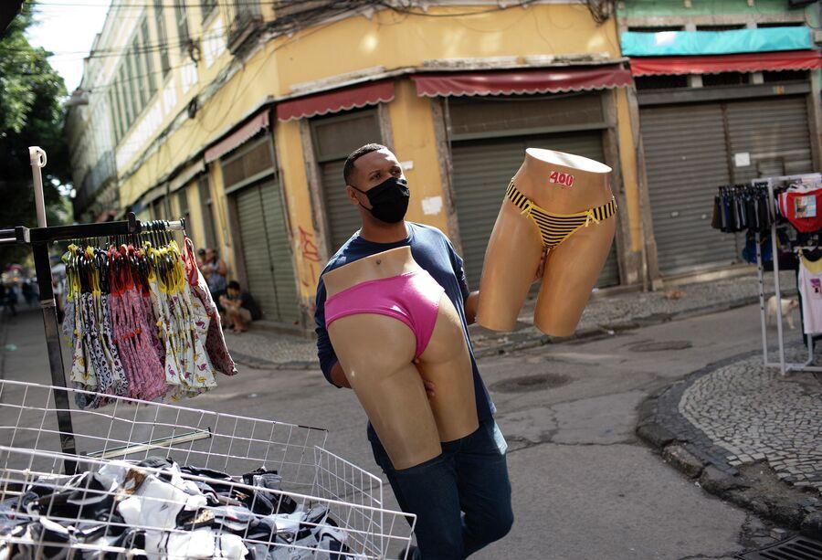 Продавец переносит манекены на уличном рынке в Рио-де-Жанейро