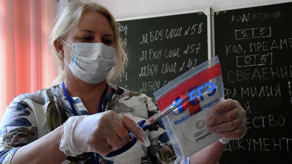 Учительница вскрывает конверт с диском, в котором содержатся задания для ЕГЭ