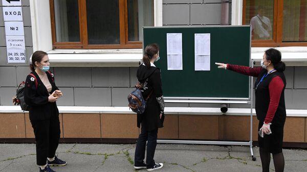 Школьница ищет свою фамилию в списках на сдачу перед началом единого государственного экзамена в средней общеобразовательной школе №13 Владивостока