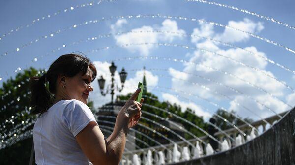 Женщина возле фонтана на Манежной площади в Москве