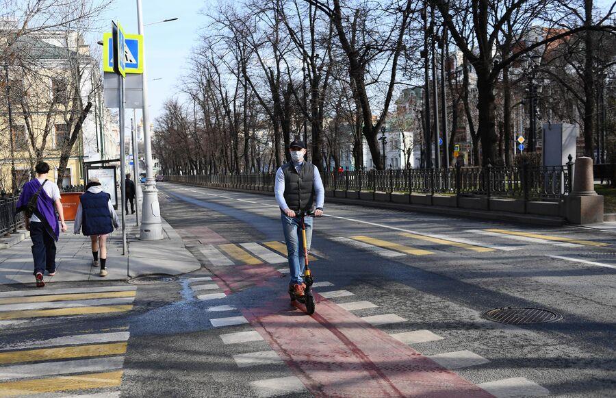 Мужчина в медицинской маске едет на самокате по велодорожке в центре Москвы.