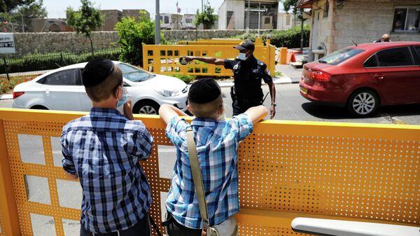 Мальчики смотрят на полицейского, который работает на въезде в еврейское поселение Бейтар-Иллит, закрытое после новых случаев заболевания коронавирусом (COVID-19)