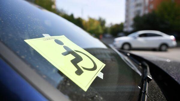 Опознавательный знак Инвалид под стеклом припаркованного автомобиля