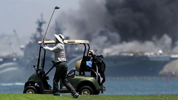 Мужчина играет в гольф на фоне горящего универсального десантного корабля USS Bonhomme Richard (LHD 6)