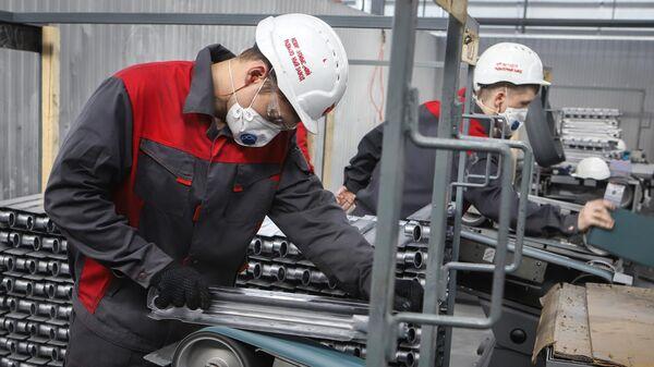 Рабочий шлифует поверхность секции в цехе механической обработки