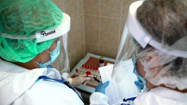 Врачи складывают пробирки с кровью для анализа перед выпиской добровольцев испытаний вакцины от коронавируса в Главном военном клиническом госпитале имени Н. Н. Бурденко