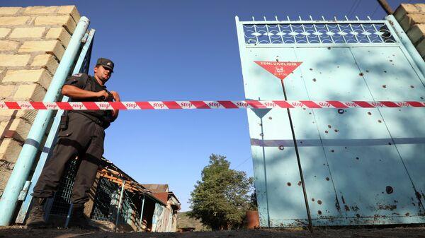 Сотрудник правоохранительных органов охраняет двор с не взорвавшимся снарядом после обстрела со стороны Армении в деревне Агдам, Азербайджан