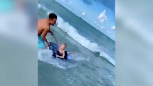Полицейский Адриан Косицки во время спасения ребенка от акулы во Флориде