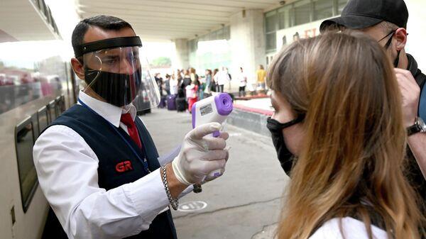 Проводник проверяет температуру у пассажиров на железнодорожном вокзале в Тбилиси