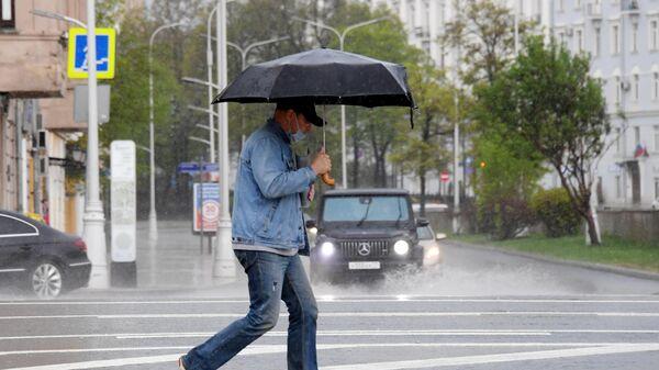 Мужчина с зонтом во время дождя