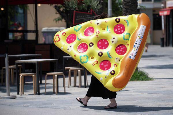 Женщина с надувным матрасом в форме пиццы в Барселоне