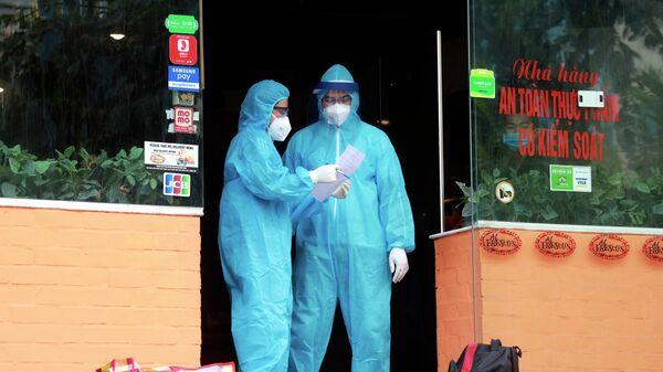 Медицинские работники у ресторана в Ханое, у работника которого диагностирован COVID-19