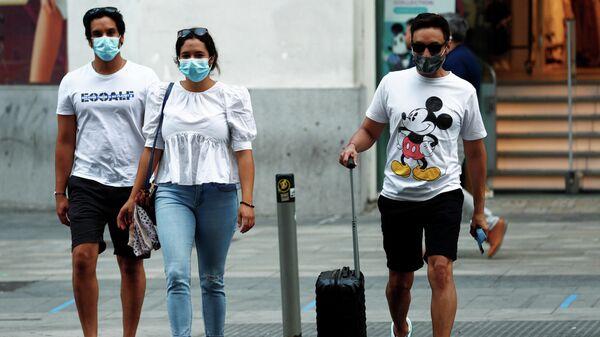 Люди в медицинских масках переходят дорогу в Мадриде, Испания