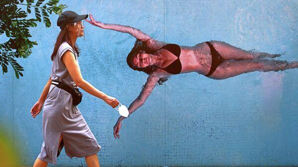Женщина в защитной маске идет по улице в Джакарте, Индонезия