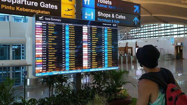 Табло в аэропорту Денпасара с информацией о рейсах, Индонезия