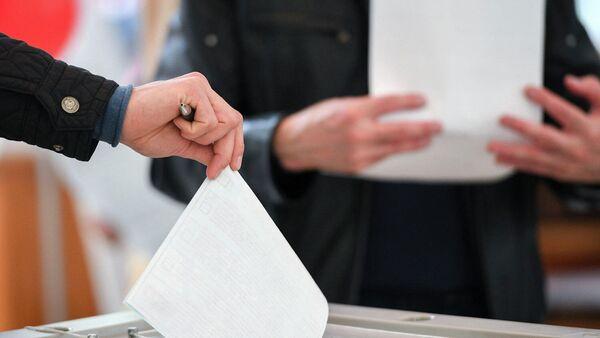 Люди голосуют на выборах