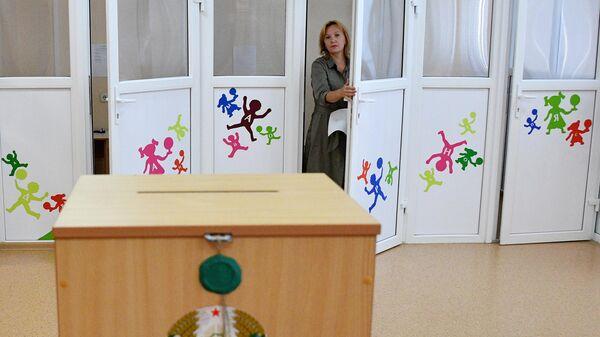 Женщина голосует на выборах президента Белоруссии на избирательном участке в Минске