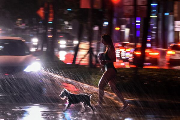 Девушка с собакой во время сильного дождя в Майами-Бич, штат Флорида